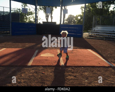 Boy playing baseball in park - Stock Photo