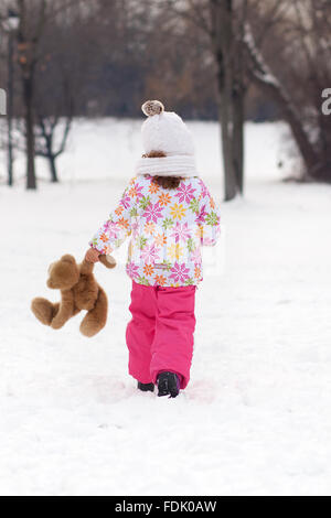 Rear view of girl walking with teddy bear on a winter day - Stock Photo