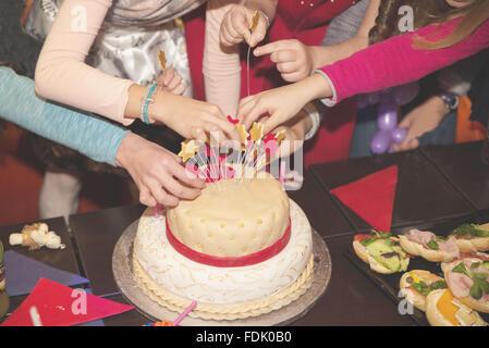 Four children decorating birthday cake - Stock Photo