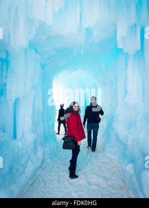 Friends walk through a tunnel at the Ice Caste in Hawrelak Park, Edmonton, Alberta, Canada. - Stock Photo
