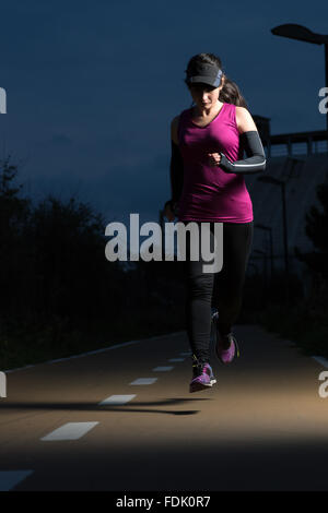 Woman running at night - Stock Photo