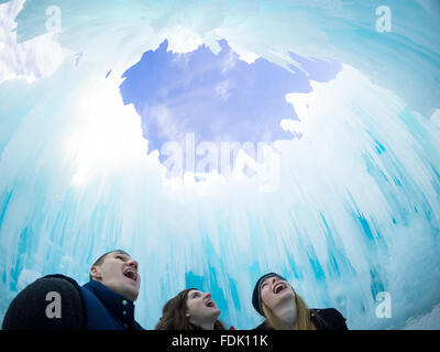 Three happy friends, with mouths agape in amazement, under the Dome Room at the Ice Castle in Hawrelak Park, Edmonton, - Stock Photo