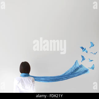 Rear view of woman with blue scarf and  origami birds - Stock Photo