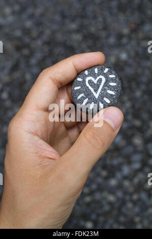 Hand holding a Heart painted on a small stone - Stock Photo