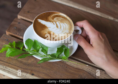 A woman holding cup of cappuccino
