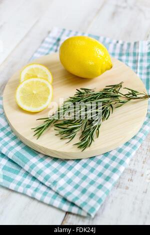 Lemon and rosemary on chopping board - Stock Photo