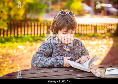 Boy reading a book in the park - Stock Photo