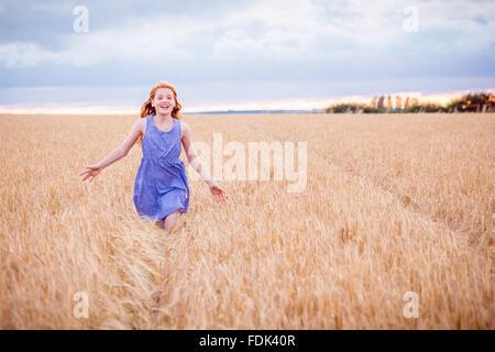 Portrait of a girl running through barley field - Stock Photo