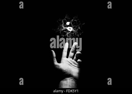Outstretched hand reaching towards electrical spark - Stock Photo
