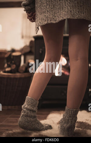 Woman standing in front of a wood burning stove - Stock Photo