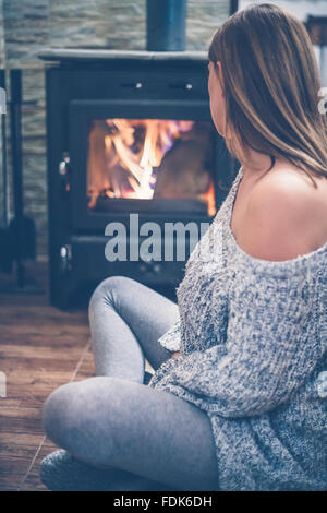 Woman sitting in front of a wood burning stove - Stock Photo