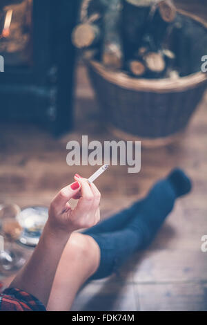 Woman sitting in front of wood burning stove smoking a cigarette - Stock Photo