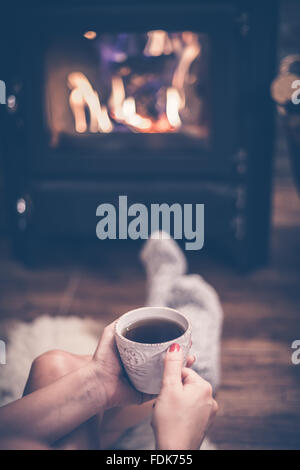 Woman sitting in front of a wood burning stove with a cup of coffee - Stock Photo