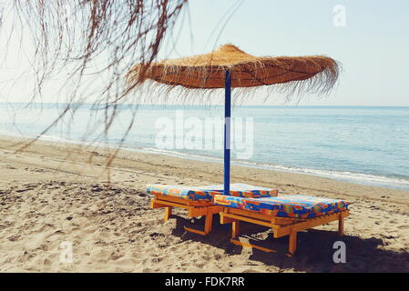 Straw parasol and two sun loungers on the beach - Stock Photo