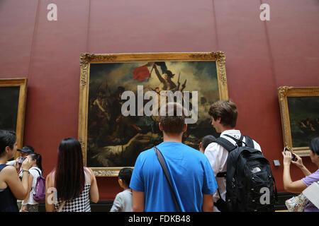 Tourist inside Louvre Museum.  Liberty leading the people, 1831. By Eugene Delacroix. Paris. - Stock Photo