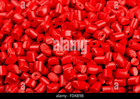 Little red plastic grains as background - Stock Photo