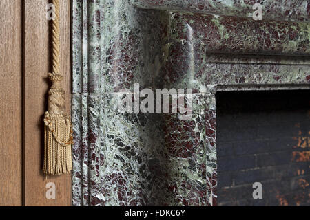 Close view of a corner of a fireplace and a bell-pull at Avebury Manor, Wiltshire, April 2011. This view was taken - Stock Photo