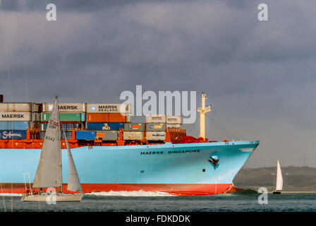 A Maersk container ship loaded with cargo negotiating the narrow channels of The Solent at the Isle of Wight. - Stock Photo