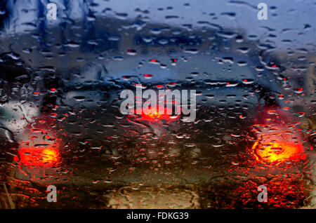 Taillights of a car seen through windscreen on a rainy day - Stock Photo