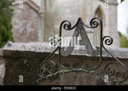 Cast iron decorative letter A and scroll work over the doorway into the gardens at Avebury Manor, Wiltshire. - Stock Photo