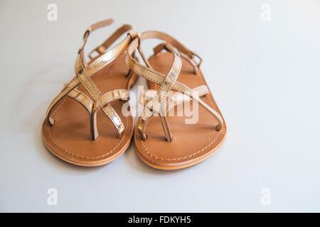 Pair of golden sandals. - Stock Photo