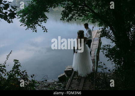 Wedding couple on the old wooden pier - Stock Photo