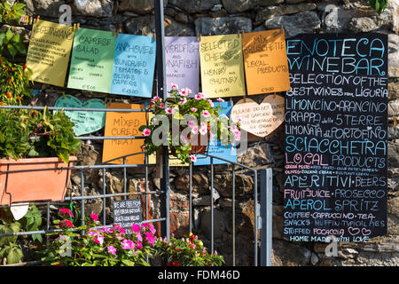 Signboards and flowers out of a cafe in Corniglia, Cinque Terre (Five Lands) National Park, Liguria, Italy. - Stock Photo