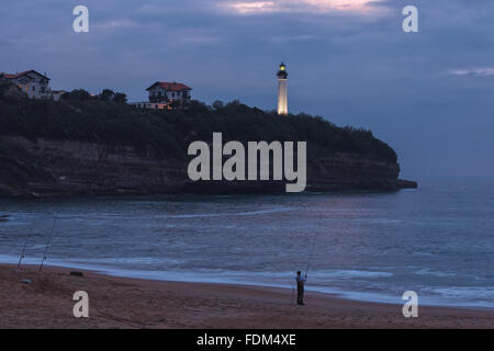 A fisherman in Chambre d'Amour Beach by twilight, with Biarritz Lighthouse in the background. Anglet, Aquitaine, - Stock Photo