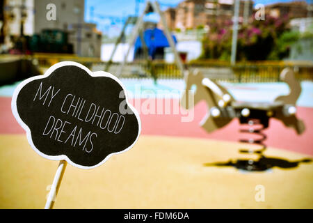 a chalkboard in the shape of a thought bubble with the text my childhood dreams in a public urban playground with - Stock Photo