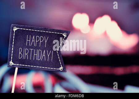 closeup of a black flag-shaped signboard with the text happy birthday, and a birthday cake with lit candles in the - Stock Photo