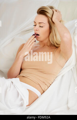 Tired woman sat in bed - Stock Photo