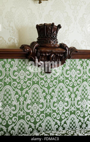 Detail of the bedstead decoration in the Green Silk Room at Dunham Massey, Cheshire. The bedstead is Victorian mahogany - Stock Photo