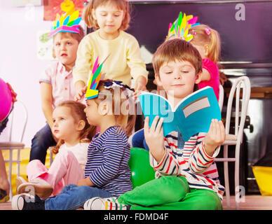 Boy learns to read in kindergarten class - Stock Photo