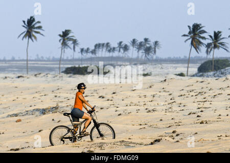 Tourist makes bike ride in Jericoacoara Beach - Stock Photo