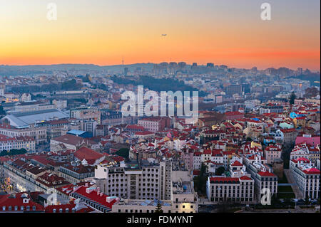 Airplane flying over the Lisbon at beautiful sunset. Portugal - Stock Photo