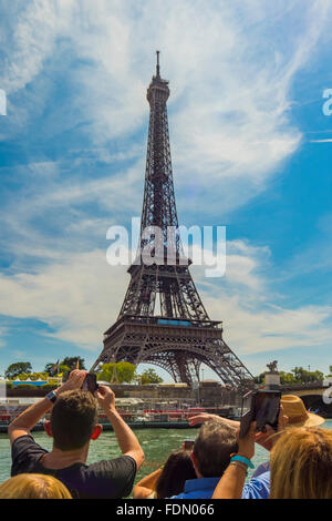 Tourist photographing Eiffel Tower from river cruise boat on Seine River in Paris. - Stock Photo