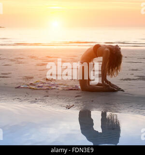 Young woman making yoga exercises on beach at sunset. - Stock Photo