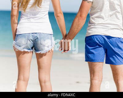 Young couple in love on the beach holding hands - Stock Photo