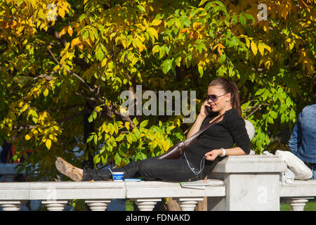 Young woman talking on mobile phone in Alexander Gardens, Moscow, Russia - Stock Photo