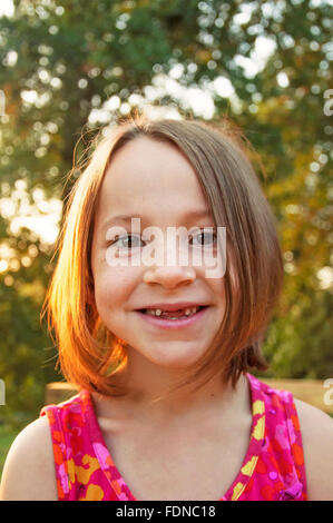 Girl smiles with front teeth missing - Stock Photo