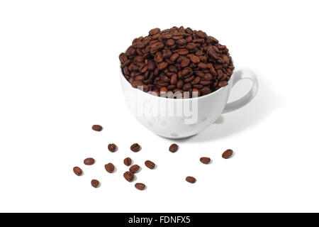 Studio shot of a coffee cup overflowing with coffee beans - Stock Photo