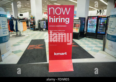 A sign prominently placed at the entrance of a KMart store in New York advertises that it is 'Now Hiring', seen - Stock Photo