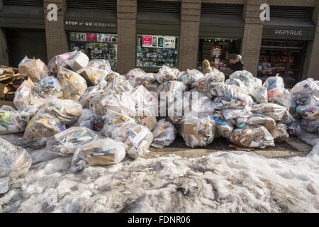 Bags of trash await pick-up in the Flatiron neighborhood of New York on Saturday, January 30, 2016. As the snow - Stock Photo