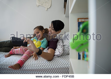 Mother and daughter taking selfie on bed - Stock Photo