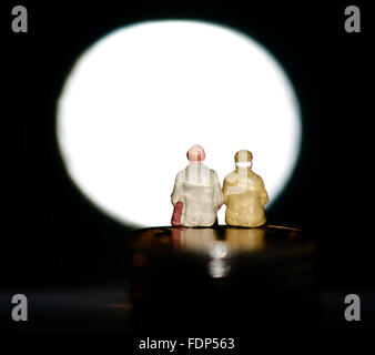 Miniature figurine pensioners sitting on coins in front of a blank spotlight - Stock Photo