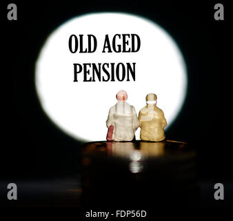 Miniature figurine pensioners sitting on coins in front of a spotlight showing the words Old age pension concept - Stock Photo