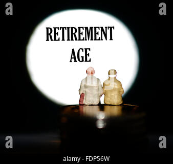 Miniature figurine pensioners sitting on coins in front of a spotlight showing the words Retirement age concept - Stock Photo