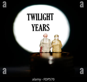 Miniature figurine pensioners sitting on coins in front of a spotlight showing the word twilight years concept - Stock Photo