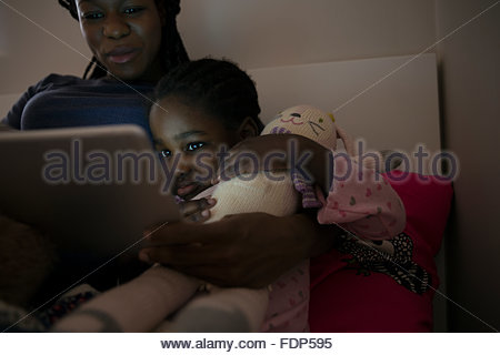 Mother and daughter using digital tablet at bedtime - Stock Photo