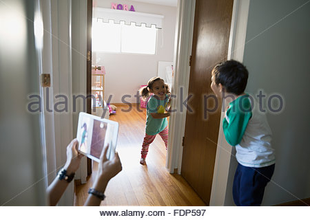 Mother photographing brother and sister playing in corridor - Stock Photo